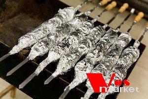 Завернутые фольгой шампуры на мангале