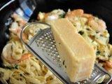 В кастрюлю с креветками и пастой добавить натертый сыр