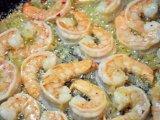 Креветки в сковородке с обжаренным луком и чесноком