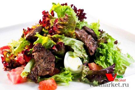 Готовый салат из куриной печени с яйцами и листьями салата